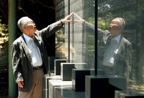 佐世保空襲で犠牲になった人々の名前を刻む墓銘碑の前で当時の記憶を振り返る臼井さん=佐世保市、中央公園