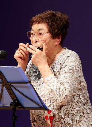 長崎市老人クラブ大会でハーモニカ演奏を披露する柴谷さん=市民会館