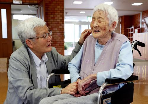 母良枝さん(右)の手を取る平野さん=6月12日、長崎市三ツ山町、恵の丘長崎原爆ホーム