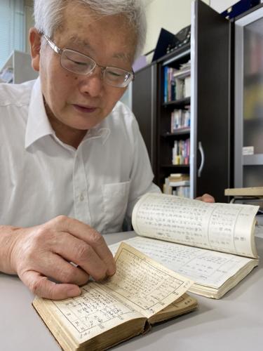韓国人徴用工の「出張日記」(手前)と、それを書き写したノートを見比べる平野さん=長崎市大黒町、平和活動支援センター