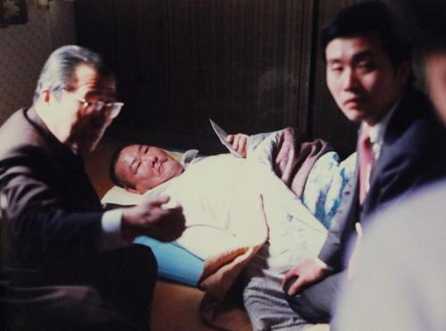 初めて訪韓し、寝たきりの被爆者を見舞う平野さん(右)=1987年、ソウル(平野さん提供)