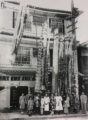 佐世保市中心部にあった「百枝外科医院」の前で家族と写る百枝薫さん(左から4人目の女性に抱えられた子ども)=1941年5月(百枝薫さん提供)