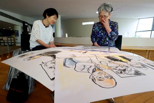 三田村さん(左)から制作に込めた思いを聞き、山口さんの目から涙がこぼれた=長崎市、長崎原爆資料館
