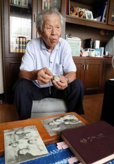 父親の形見の懐中時計を手に引き揚げの苦労を語る増田さん。手前は当時の家族写真=大村市富の原1丁目の自宅