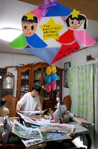 自宅で紙芝居の制作をする三田村さん。子どもたちからもらった感謝の手紙は宝物だ=長崎市内