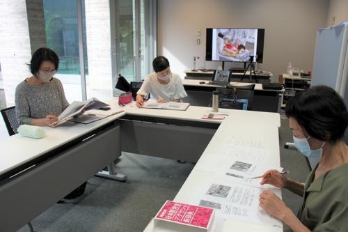 平野さん(右)の助言を受けながら、朗読の流れを考えるメンバー=国立長崎原爆死没者追悼平和祈念館